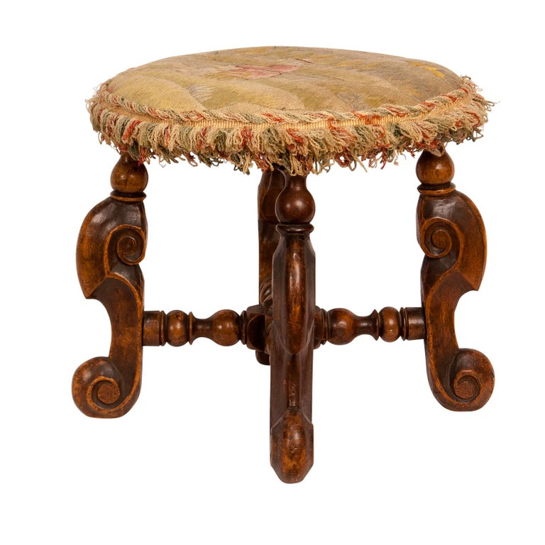 An early 17th century French walnut Louis XIII period foot stool, circa 1620. Great color and patina. Upholstered in crewel needlework probably associated.