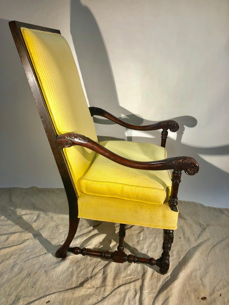 A Louis XIII style upholstered armchair in carved walnut, circa 1940, currently upholstered in yellow cotton fabric.