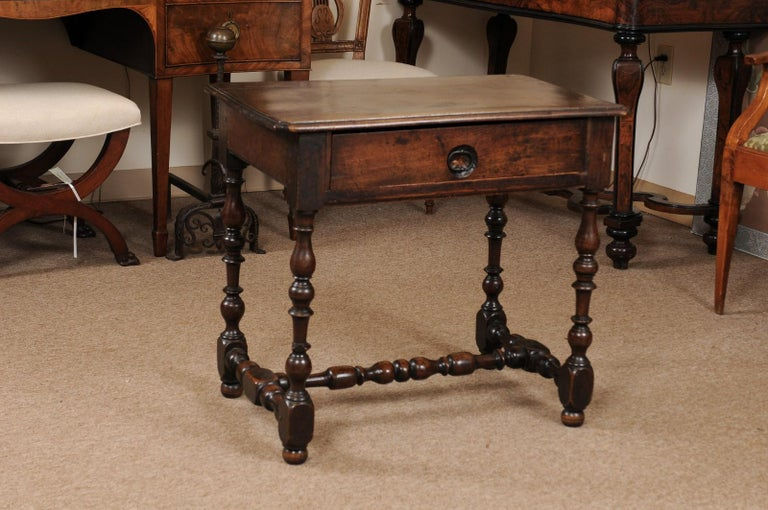 A Louis XIII walnut side table originating from France and dating late 17th century. The rectangular top with molded edge above a center in frieze. All resting on turned legs and stretcher ending in bun feet.
