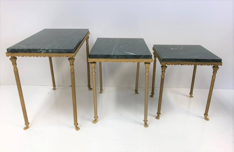 Louis XIV style bronze & marble nesting tables. Decorative bronze frame has columned style legs with feet. Green marble tops. Larger table measures: 17 H x 12 D x 19.75 W.