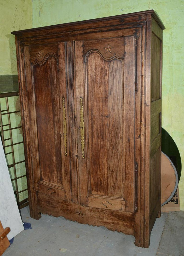 Handsome two-door antique French Louis XIV to XV transition period wardrobe armoire. Two recessed panel doors with metal inlay stars and diamond decoration. Spacious interior armoire with original hardware.