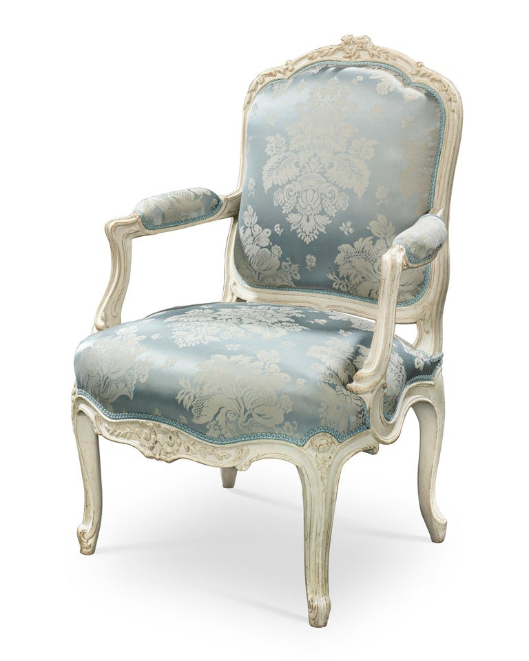 This impressive pair of French armchairs displays the splendor and elegance of the Louis XV period. Crafted by the famed ébéniste Jean-René Nadal l'Ainé (1733-1783), the chairs are exquisitely constructed with graceful, curving lines and elegant