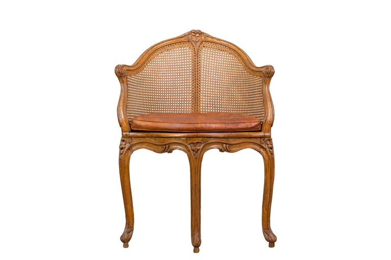 A Louis XV period beechwood and cane fauteuil de bureau, the curved crestrail with a carved central rosette terminating in molded downswept arms above a shaped seat resting on molded cabriole legs. Retains an antique tooled leather cushion, circa