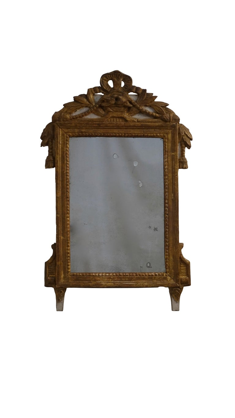 Louis XV hand carved and gilt boudoir mirror with parcel gray painting. Having a tied ribbon cartouche above a pair of love birds with tasseled cord and laurel leaves. Original mirror shows expected clouding and age. France, mid 18th century.