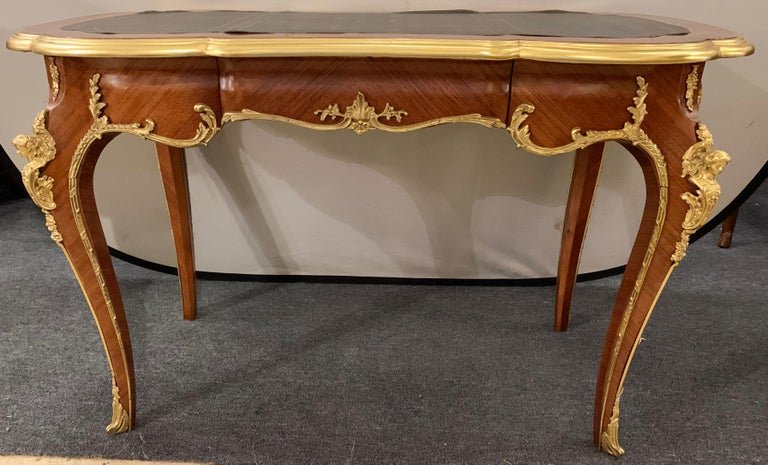 Louis XV Francois Linke style ladies desk having heavy solid bronze mounts. The corners depicting full busted woman leading to curved legs of bronze framing on bronze sabots. The whole supporting a tooled leather top. This desk can sit center room