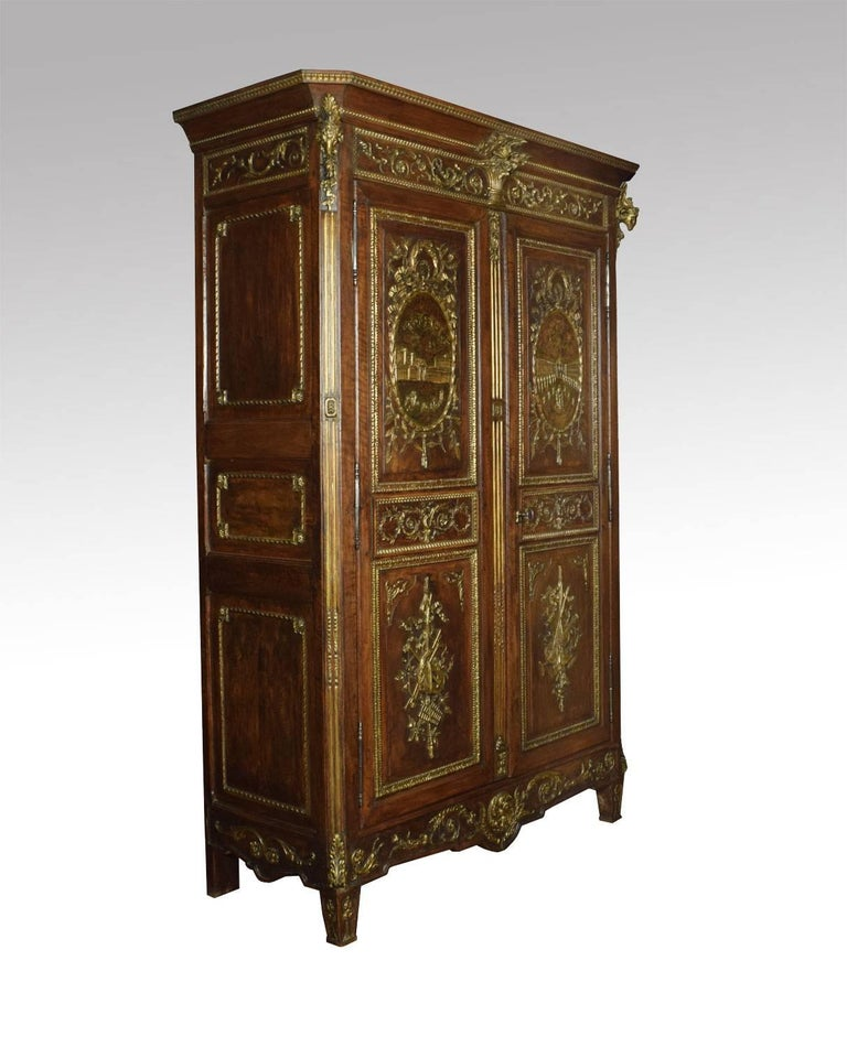 Louis XV French walnut armoire, the projecting cornice surmounted with carved ram's heads, above two large paneled doors with detailed gilded scenes incorporating baskets of flowers and trailing festoons, with architectural vistas and musical