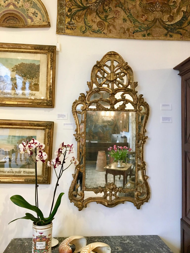 Louis XV circa 1750 Provincial, carved giltwood mirror with mirror borders, and scrolling foliate and musical motifs throughout. In excellent and overall original condition.