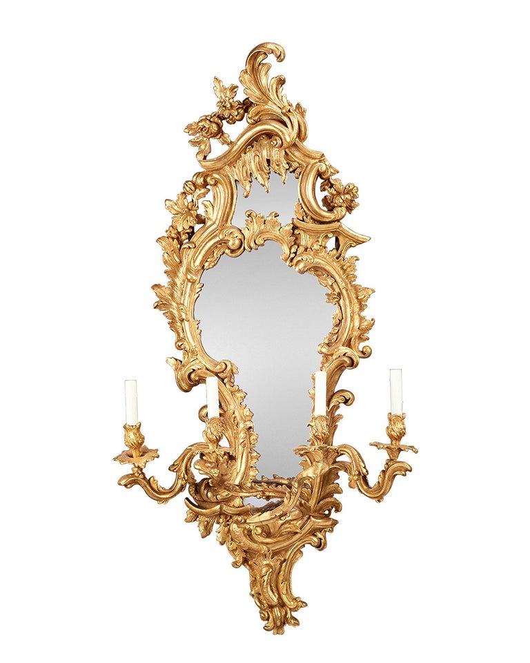 This incredibly rare pair of Louis XV-period giltwood mirrored girandoles capture the grandeur, grace and opulence of the Rococo movement in the decorative arts. Each opulent mirror is exquisitely framed with voluminous flourishes of naturalistic