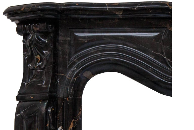 French Rococo Louis XV fireplace mantel made in a superb Potoro marble. Hand carved molded shelf above a paneled frieze, centered by an elaborate scrolled cartouche enclosed on the end blocks set above the angled scrolled jambs.