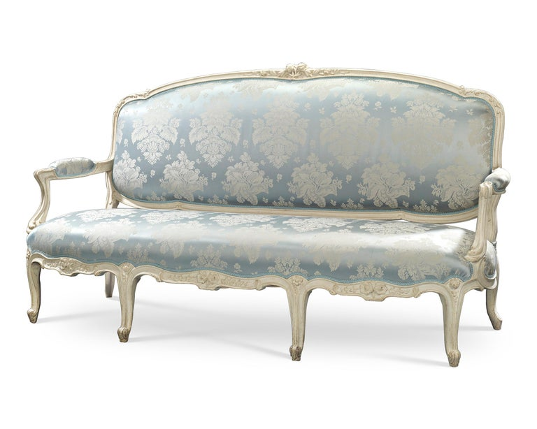 The splendor of the Louis XV period is captured in this incredible settee by the famed ébéniste Jean-René Nadal l'Ainé (1733-1783). Beautifully upholstered in blue and white fabric that complements the white of the wood, the rare sofa reflects the