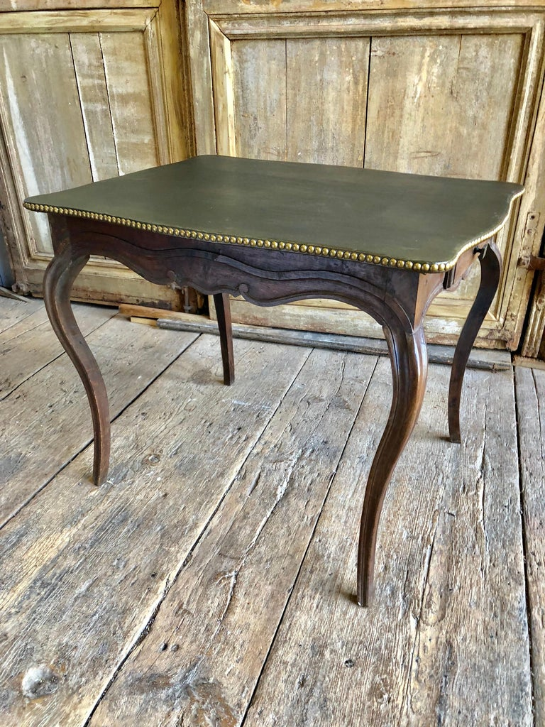 An 18th century leather-top side or card table circa 1780 in oak, with a dark green leather top with brass nail details, two small drawers in the scalloped apron on slender cabriole legs.