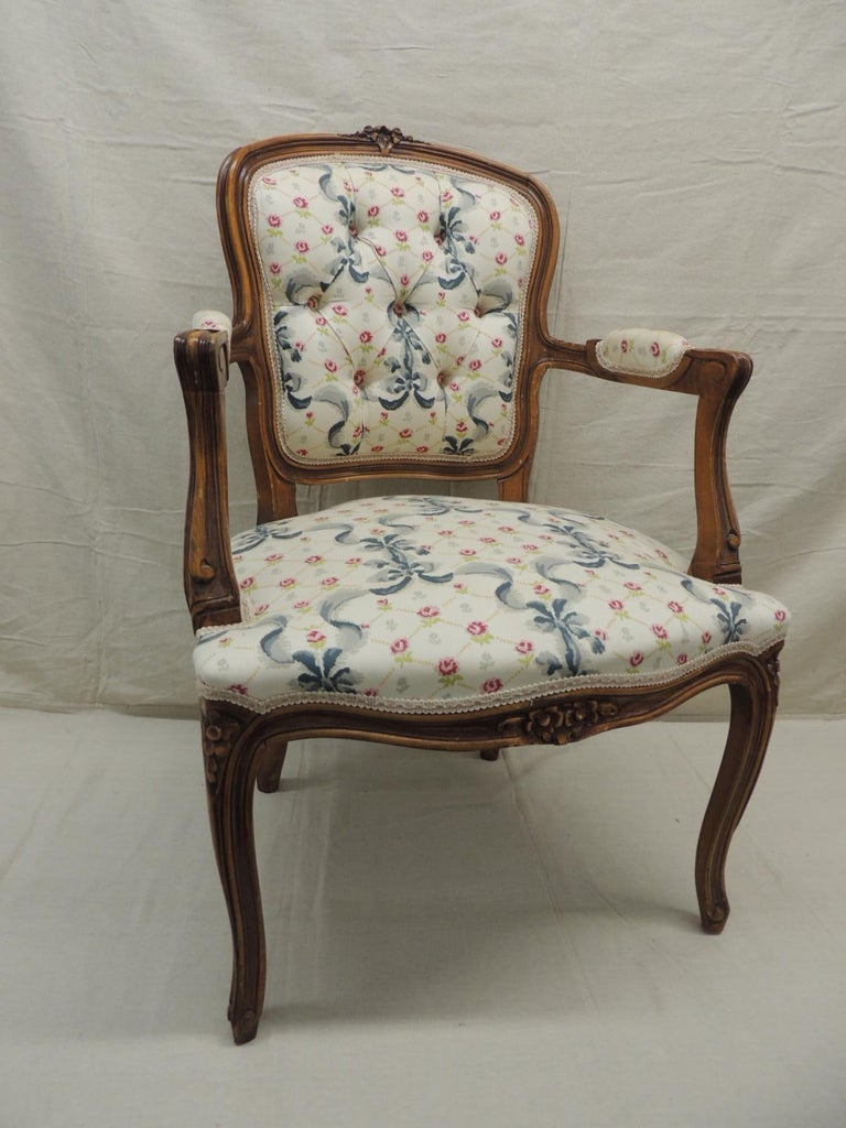 Louis XV style antique petite armchair. Floral and ribbon cotton fabric upholstery. In shades of green, blue, pink on an off-white background. Honey color wood frame with padded arms. Taffeted back trim with pink, green and natural gimp all