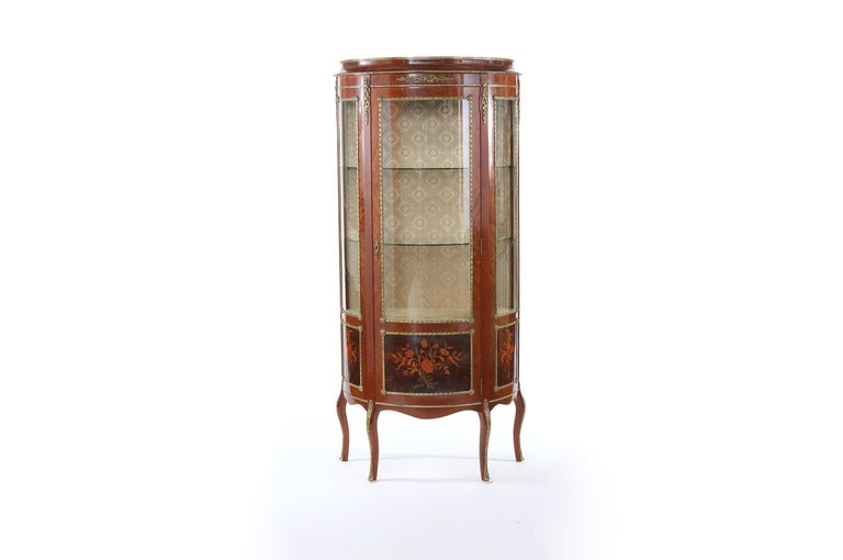Louis XV style bronze mounted China display cabinet / Vitrine with exterior inlaid design details. The interior of the cabinet has two glass shelves and lined with gold patterned brocade. The cabinet stands on cabriole legs with Ormolu mounts. The
