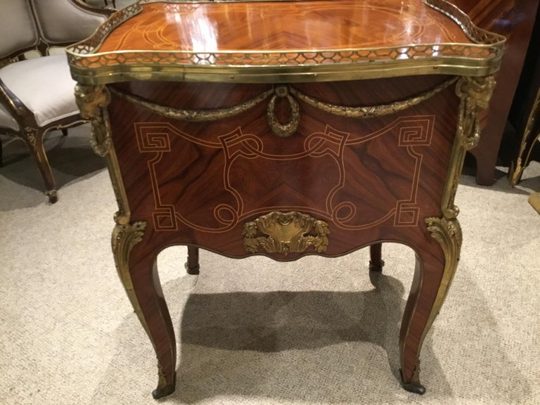 Early 20th century, the rectangular top with projecting corners and a three-quarter pierced brass Gallery, above a conforming case fitted with three drawers, all with applied mounts, raised on Cabriole legs ending in sabots, the whole with