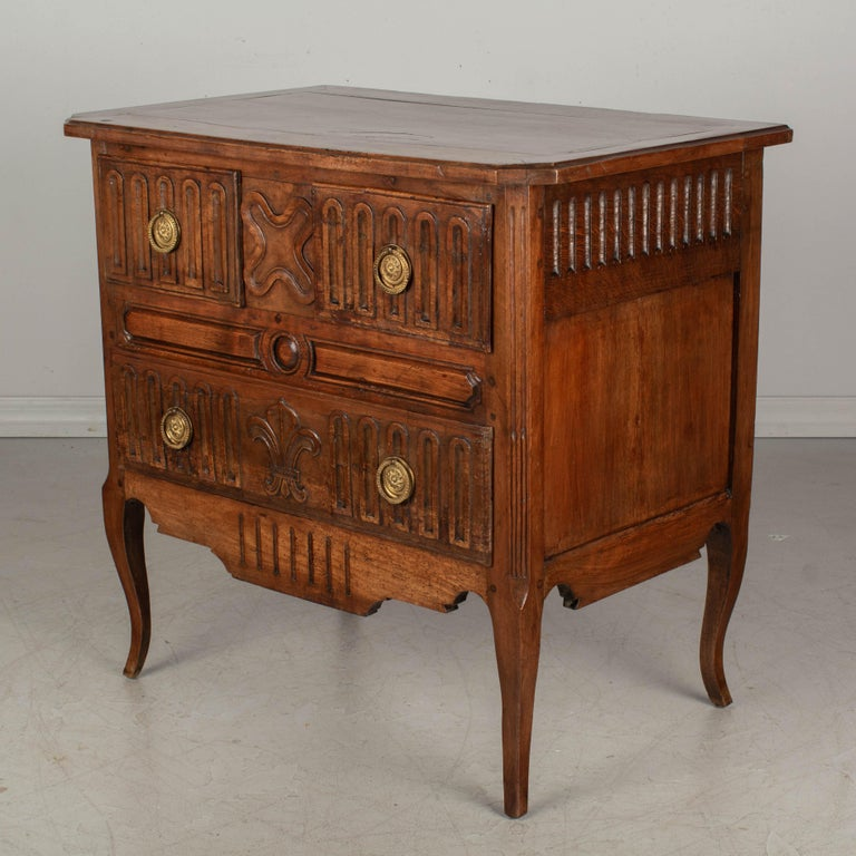 A Country French commode, or chest of drawers, made of solid walnut, cherry and fruitwood. Three dovetailed drawers with brass ring pulls. Hand carved decoration including a large Fleur de Lis on the bottom drawer. Beautiful quality to the wood with