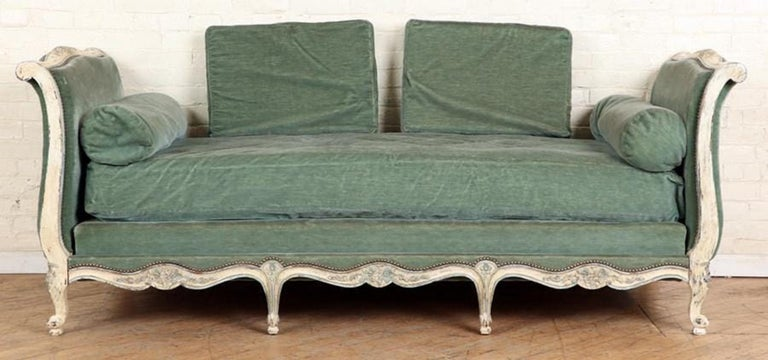 A Louis XV style sleigh-form day bed, the frame carved with flowers and other decoration, in distressed white and blue painted finish with blue/green vintage mohair upholstery and cushions.