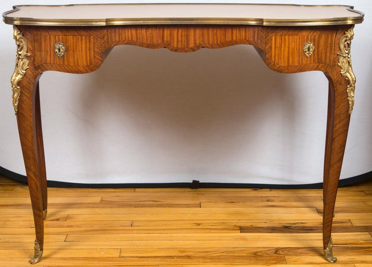 A fine French kidney shaped bureau plat desk, having an inset beige leather top. Two side drawers over cabriole legs with ormolu mounts.