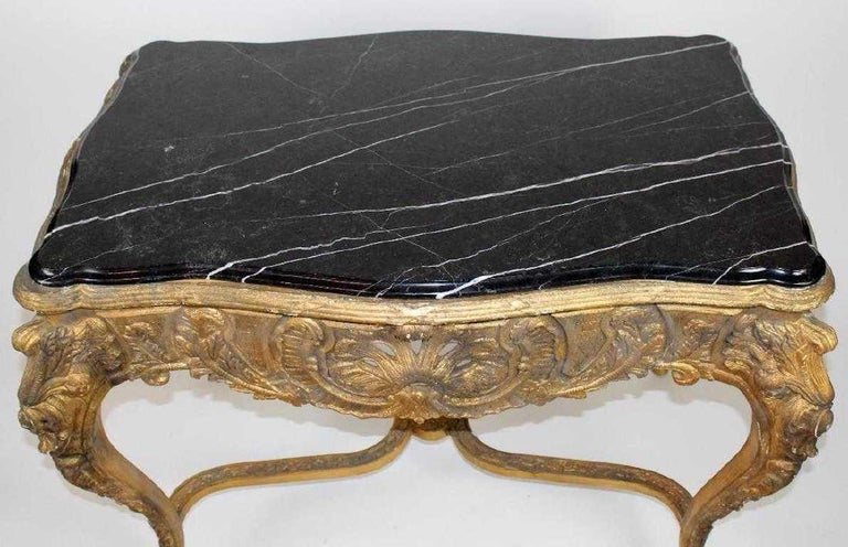 A Louis XV style gilt console table with marble top. The black serpentine-cut marble top flows gracefully over the conforming gilt wood console table base. The scalloped apron features an open-work rococo shell as well as acanthus leaf and foliate