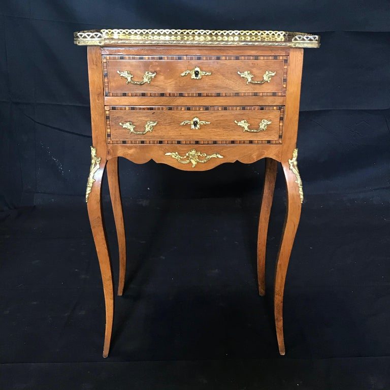 Sumptuous French Louis XV style walnut inlaid nightstand or side table having two dovetailed drawers above a carved apron and exquisite gold fretwork and ormolu decoration. The fruitwood and ebony geometric inlay is exquisite. #5777  Measures: H