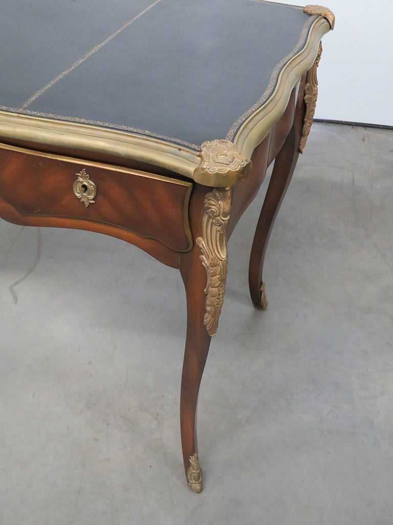 Louis XV style leather top desk with brass trim and accents and three drawers.