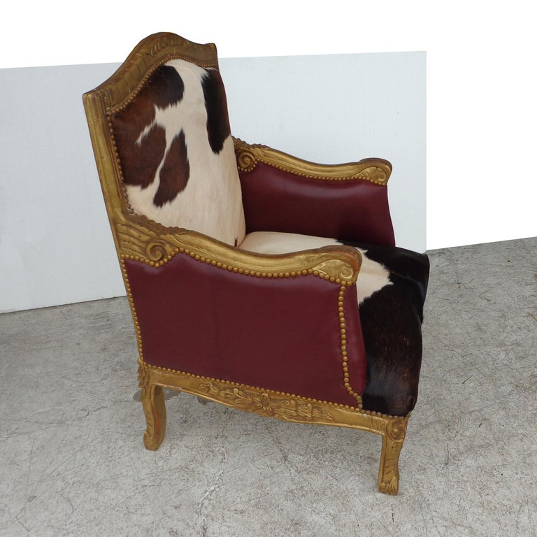 Louis XV style lounge chair in cowhide   In cowhide with leather sides and back. Gilt carved frame.