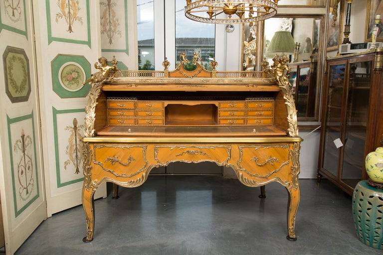 This is a stately and lavishly decorated Louis XV style cylinder desk. The top with a pierced brass gallery centered by an inverted arched pediment with cherubs. The top is flanked by four prominent brass figural putti and candle holders above an