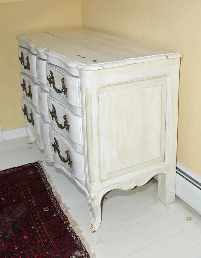 The Louis XV-style dresser is painted white and has three drawers with large elaborate metal handles The sides are paneled in the French manner.