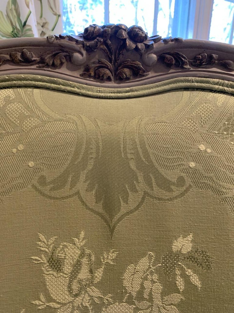 Louis XV style carved cream painted and gilt beechwood frame pale green damask upholstered bergère, having an arched cresting of carved gilt flowers and exuberant wings, padded arms and fluted arm supports , loose seat cushion and throw pillow,