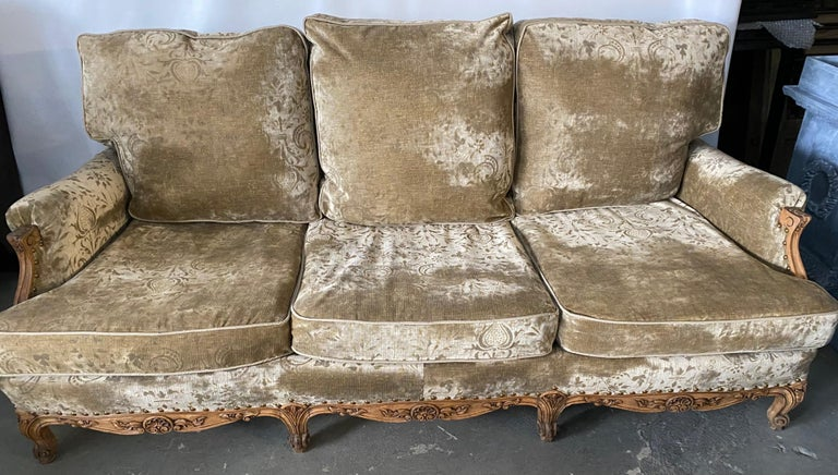 Grand French over stuffed sofa or canapé made in the Louis XV Provincial style featuring large triple loose back and seat cushions. Sofa made with generous proportions providing extra comfort. Supported by eight hand carved cabriole legs, the frame