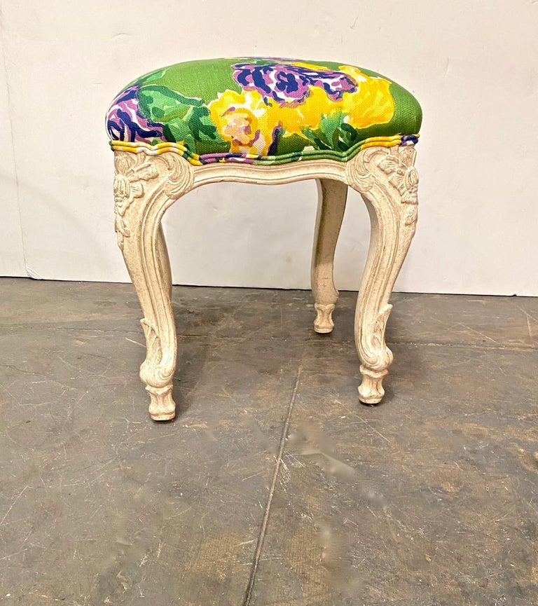 This is a beefy well-carved set of three Louis XV style tabourets/stools. The upholstery features a bold tropical patterned printed linen that bring Miami-style to mind. These three stools would make a statement placed at the end of a bed or in