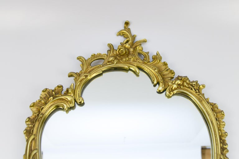 Beautiful oval shaped French Rococo style or Louis XV style wall mirror in bronze, decorated with C-scrolls, rocaille and floral motifs, circa 1950s. Dimensions: Height 70 cm / 27.55 in, width 42 cm / 16.53 in depth, 2 cm / 0.78 in.