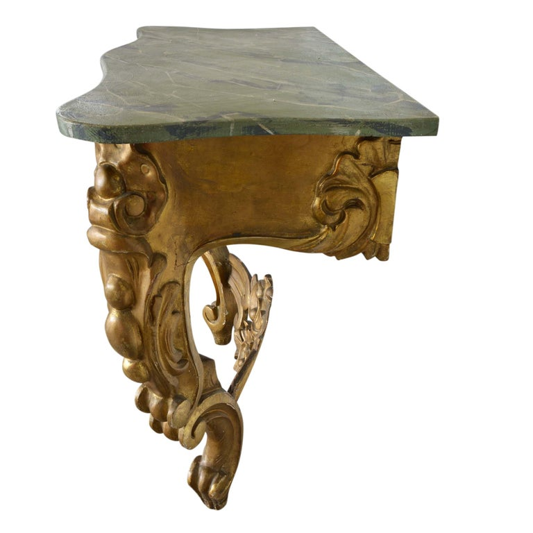 An outstanding carved giltwood console in the Louis XV style, it was likely carved early in the 20th century. The faux marble top is expertly painted to appear as rich green marble. The console top sits atop a refined base of giltwood with scrolled
