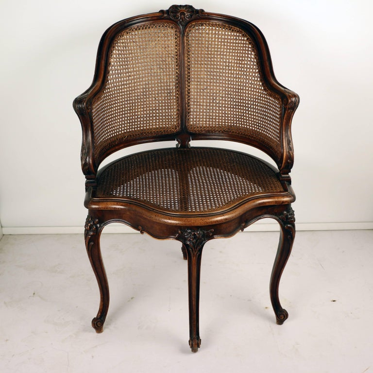 This shapely corner armchair has unusually positioned legs. The curving arms ,legs and caned sides and seat all contribute a sense of lightness , the carving is excellent.