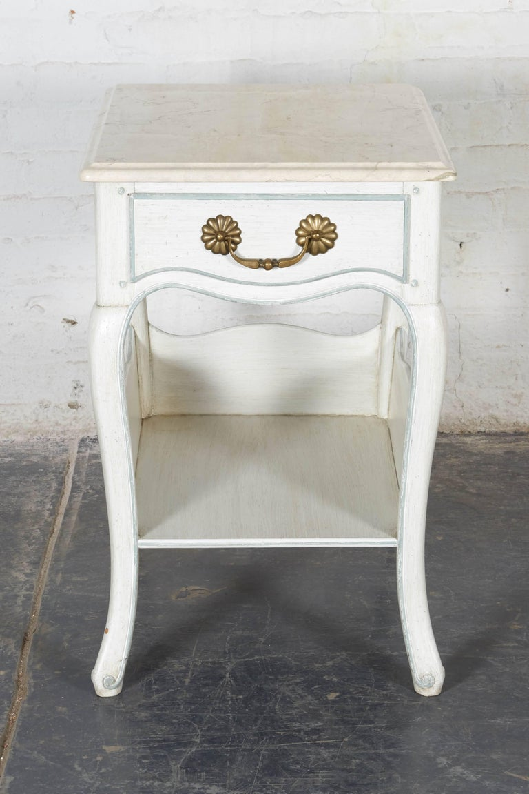 Each with marble top over a frieze drawer with patinated brass hardware; raised on cabriole legs with a platform stretcher. Painted in an antiqued white with pale blue detailing.