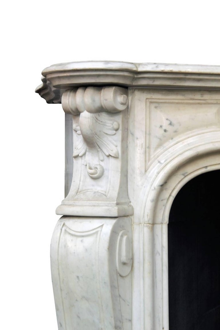Large French Louis XV style mantle fireplace in white Carrara marble, 19th century. Refined and sinuous shapes and overall very minimalist, this elegant antique Louis XV style fireplace was made of Carrara marble during the 19th