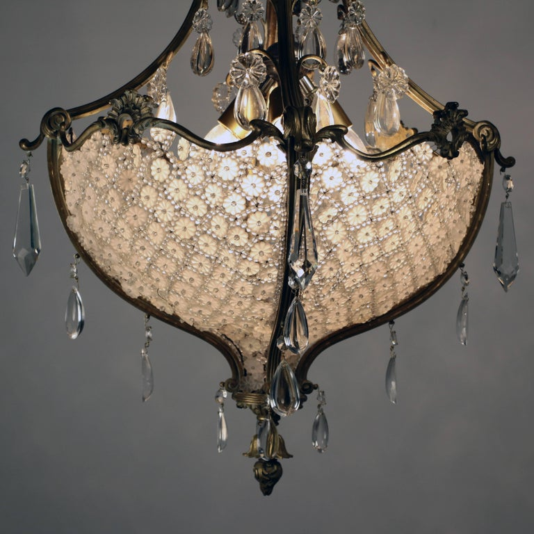 This sumptious chandelier from the Belle Epoque consists largely of a large hemispherical bag filled with basket weave crystals in a lattice of beads and flowerheads, the upper section complements and echos this arrangement. See the attached photos