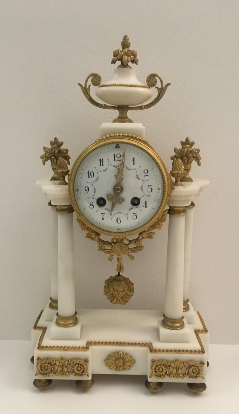 Elegant 19th century French Louis XVI gilt bronze mantel clock and two candelabras in antique white Carrara marble and gilt bronze. The white enamel dial with hands finely worked and gilded, the dial reveals part of the mechanism. The strings of the