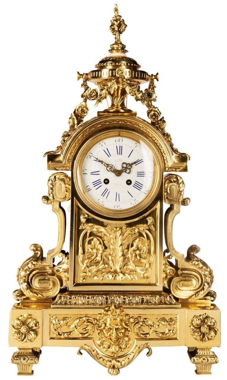 A very good quality ormolu mantel clock having an urn finial with floral swags, white enamel clock face with Roman numerals, an eight day striking movement, classical scrolling mounts to either side, raised on a plinth base with a bearded mask to