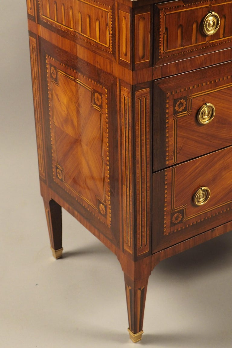 Wood commode with two bottom and three top drawers, the surfaces inlaid with contrasting marquetry work throughout, original bronze hardware and a mottled beige-brown marble top.