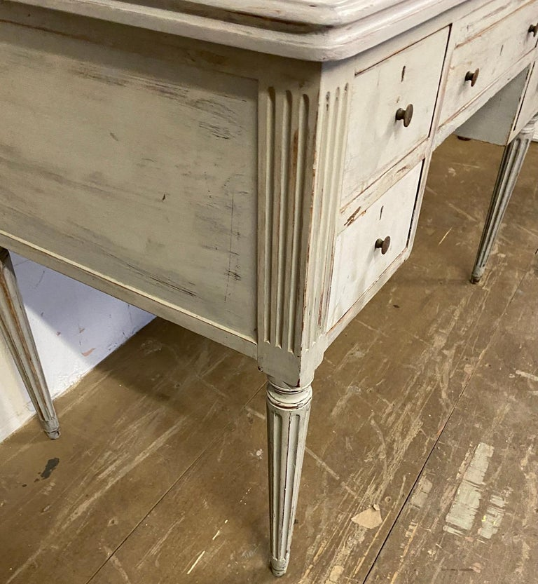 This painted rectangular shape Louis XVI style desk stands on four fluted tapered legs. The writing table has two stacked drawers on each side and a drawer in the middle for plenty of storage. Desk is hand painted in a grey palette. The table can