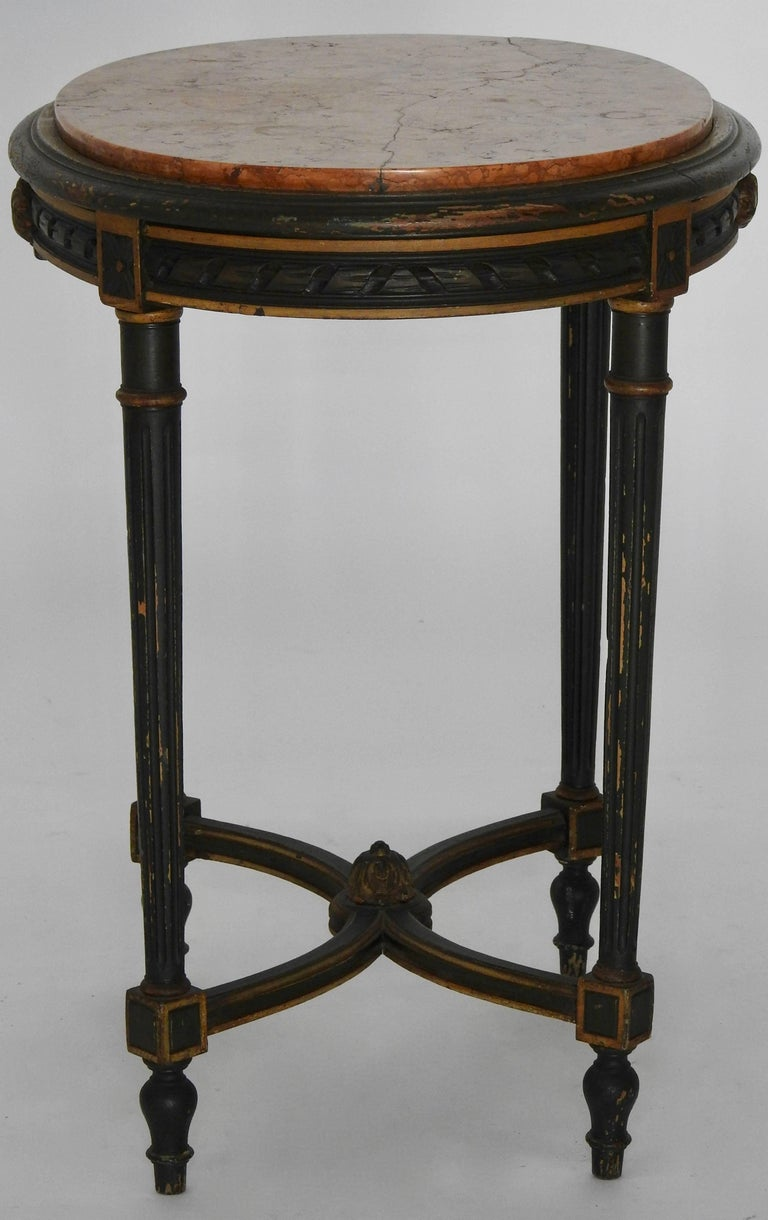 This table is in a gorgeous dark green paint with gilding detailing. The marble is of warm red tones. The marble has had a repair done. Table stands on four round tapered legs with curved stretchers. Decorated with finials and carving details.
