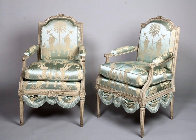 Louis XVI French silk armchair, Claude II Sené Fauteuil a la Reine, early 1780s. Arched, padded back with stylized flowerhead hand carved topsail, similarly poetic hand carved seat rail. Raised on gracefully tapering, fluted legs. Reupholstered in