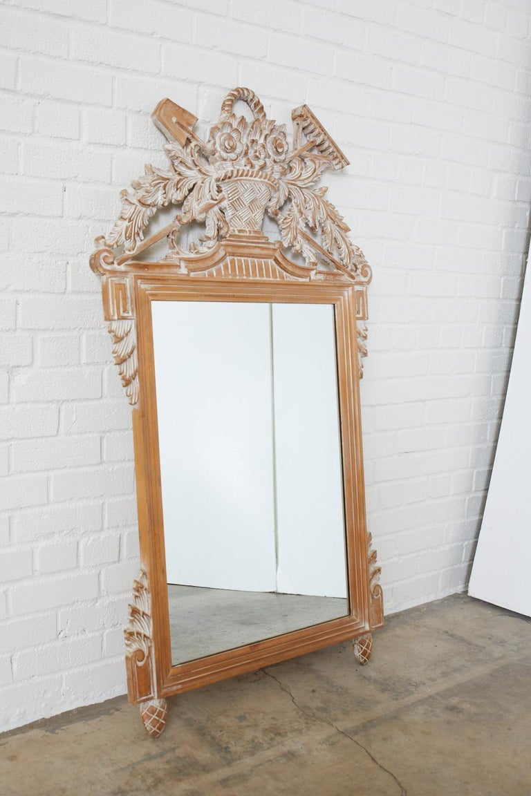 Hand carved oak wall mirror with a garden motif featuring a basket of flowers with cascading acanthus leaves and garden tools made in the Louis XVI style. Sits on pinecone feet with foliate accents on each corner. Has a white washed finish.