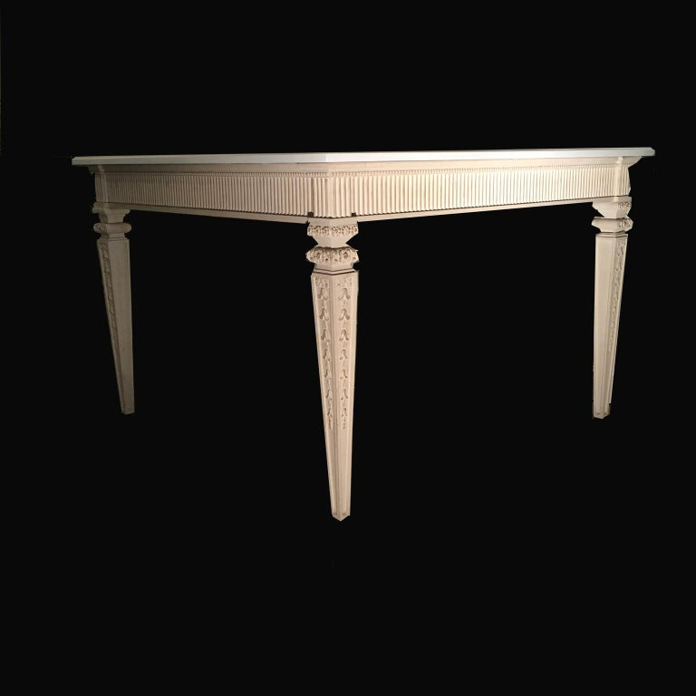 This is an elegant French dining table in solid oak, with rich hand-carved details on the legs. It is white hand-painted on the top and in ivory color on the bottom. It is perfect for an elegant dining room or a modern kitchen. Beautiful square