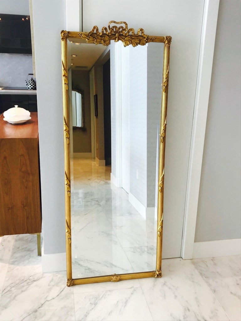 Outstanding 1940s gold leaf mirror with exquisite ribbon pediment top. Mirror features a fluted frame with hand carved foliage and floral designs, and with stylized carved Fleur-de-Lis corner accents.