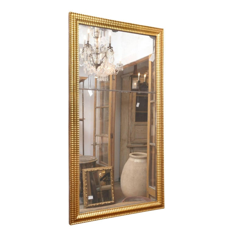 Louis XVI gilded mirror, two tones of gilding adorn frame surrounding a bipartite mirror plate. Mirror's reflection is near-pristine with only a few age spots. Subtle amounts of diamond dust cluster around mirror's edges and joint where the two
