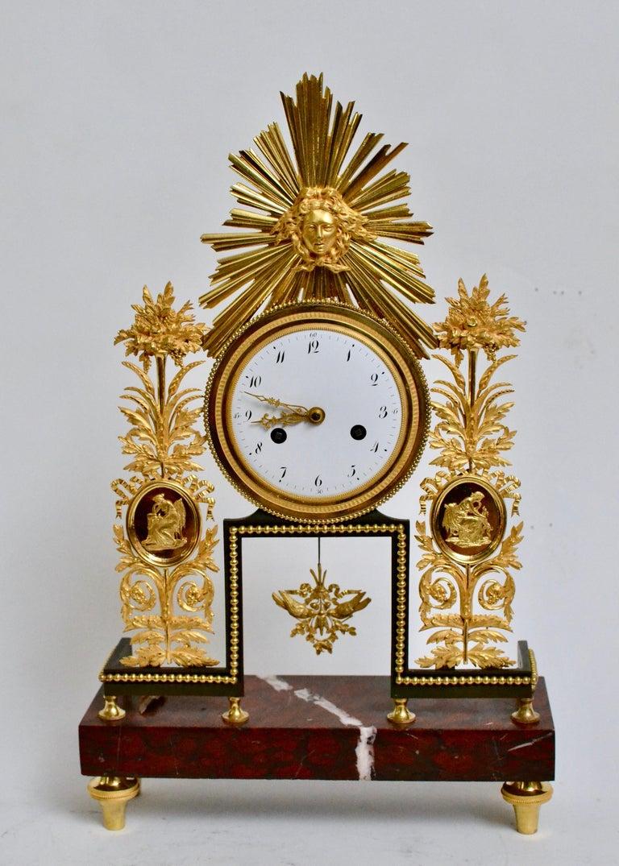 A Louis XVI gilt bronze and marble mantel clock.
