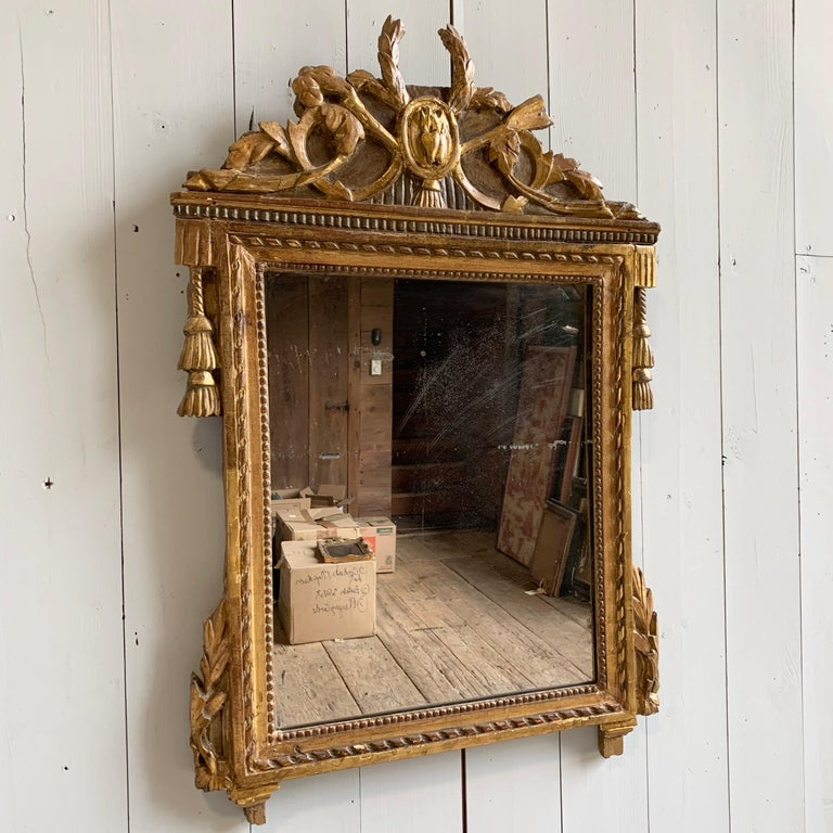 A French Louis XVI period giltwood wall mirror with upper crest and other carved decoration including tassels, garlands, etc. Original mercury plate glass mirror, circa 1790.
