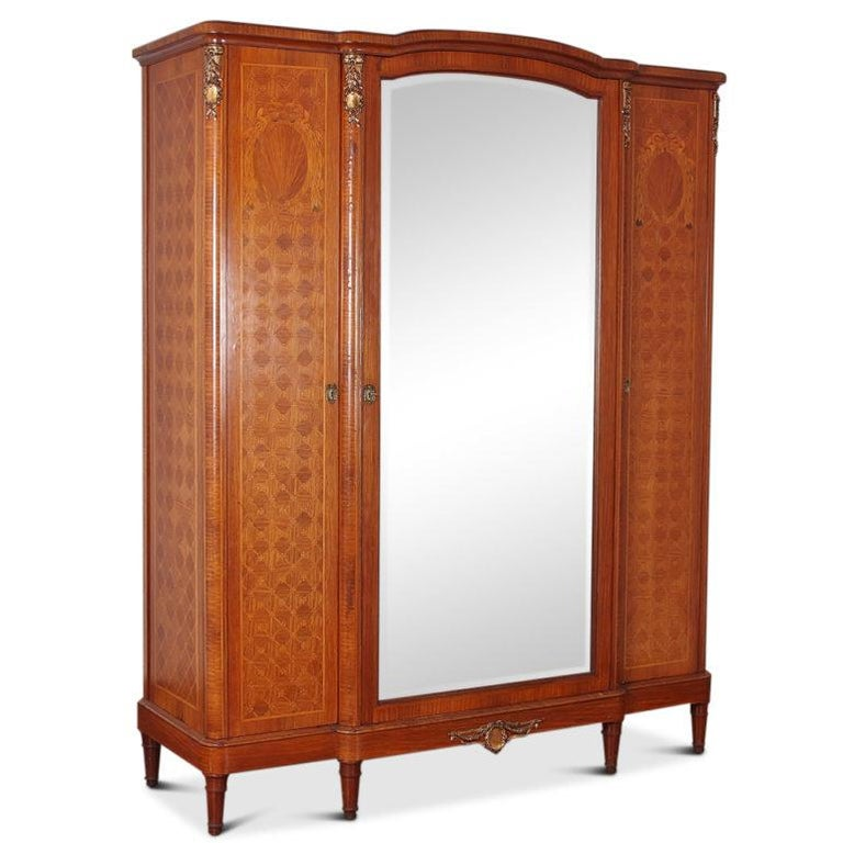 Fine-quality, French inlaid Louis XVI-style 3-door armoire, featuring inlaid classical motifs on a parquetry background. The interior has adjustable shelves on each side and a central section for hanging. There is a custom-fitted three-drawer chest