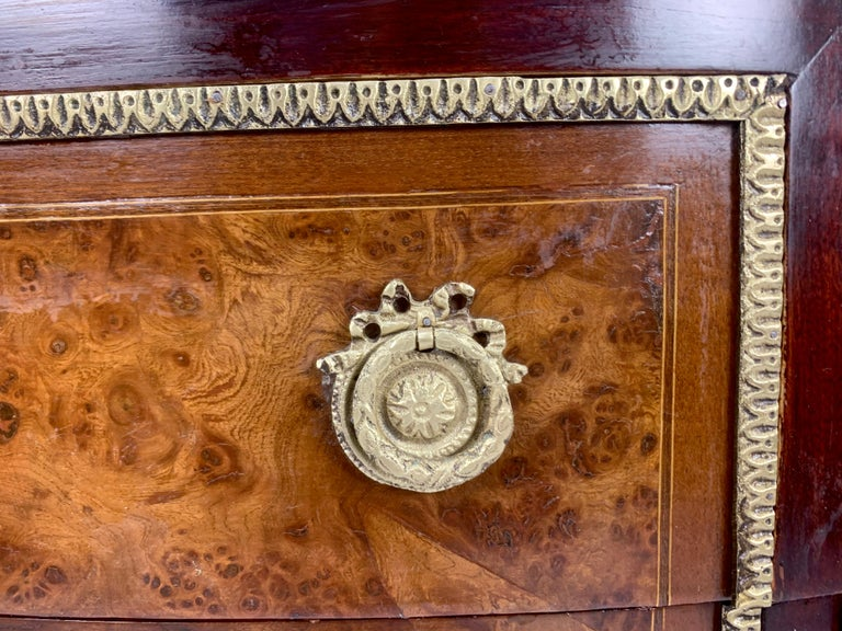 Exquisite French Louis XVI demilune commode with original marble top features beautiful bronze mounts and pulls.